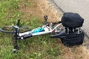 mountain bike laying on the side of a road.