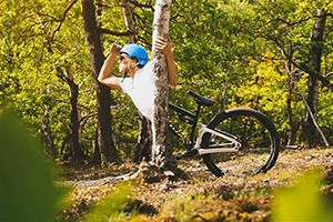 person standing near a mountain bike in the woods