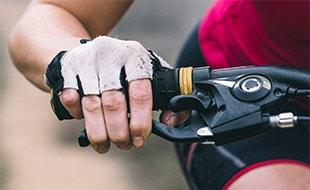 Hand on mountain bike handlebar with gloves