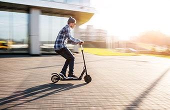 man riding a kick scooter