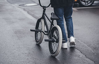 someone walking down the street with a bmx
